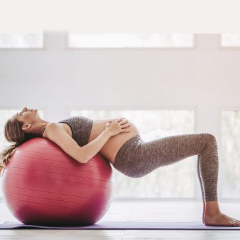 Beautiful pregnant woman workout. Doing yoga with fitball.